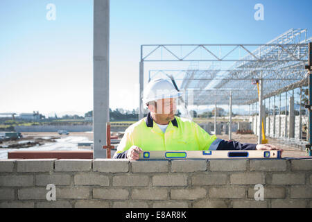 Builder using spirit level on construction site wall - Stock Photo