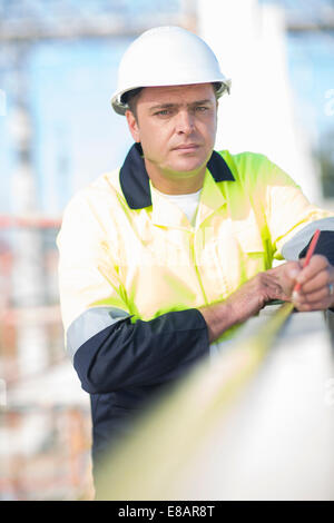 Builder using tape measure on construction site wall - Stock Photo
