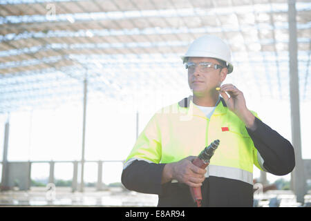 Builder with electric drill inserting earplugs on construction site - Stock Photo