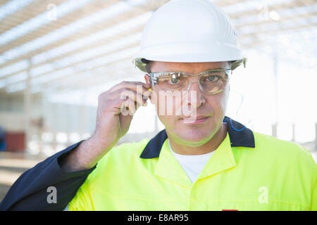 Builder with safety glasses inserting earplugs on construction site - Stock Photo