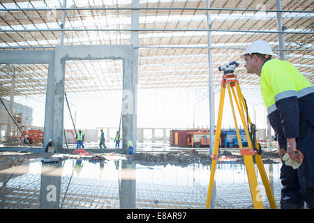 Surveyor using tripod and level on construction site - Stock Photo