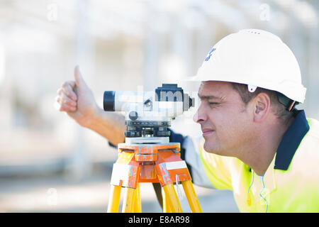 Surveyor looking through level on construction site - Stock Photo