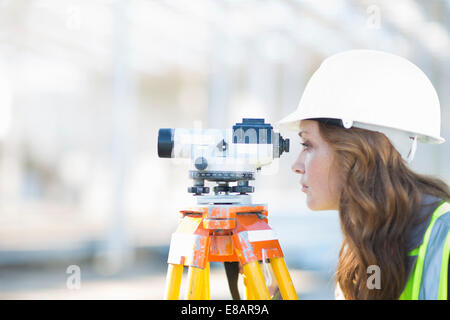 Female surveyor looking through level on construction site - Stock Photo