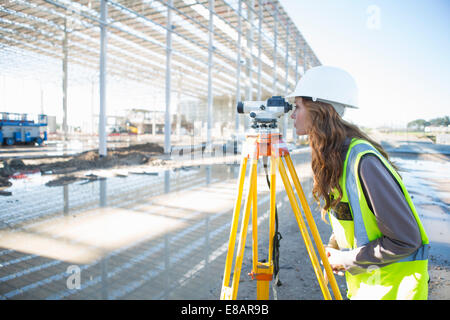 Surveyor leaning forward to look through level on construction site - Stock Photo