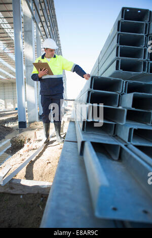 Site manager checking girders on construction site - Stock Photo