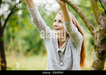 Young woman in field holding on to tree branch