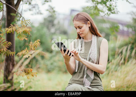 Young woman using digital tablet in field - Stock Photo