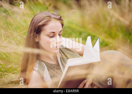 Young woman sitting in long grass reading book - Stock Photo