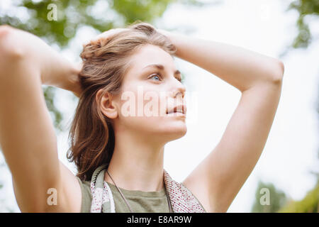 Serene young woman gazing up with hands in hair - Stock Photo