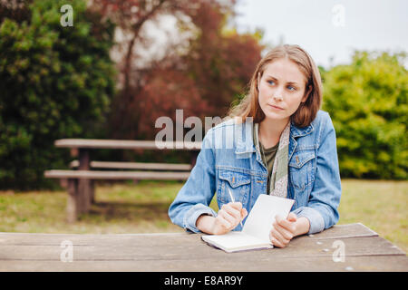 Young woman sitting at picnic bench in park writing in notebook - Stock Photo