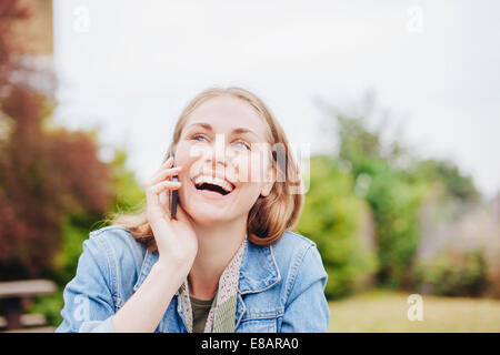 Young woman laughing whilst chatting on smartphone in park - Stock Photo