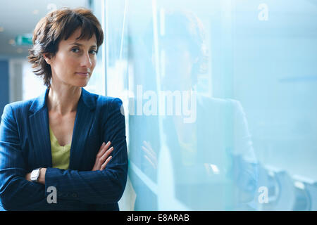 Portrait of mature businesswoman leaning against glass wall with arms crossed - Stock Photo