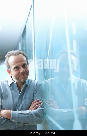 Confident mature businessman leaning against glass wall in office - Stock Photo