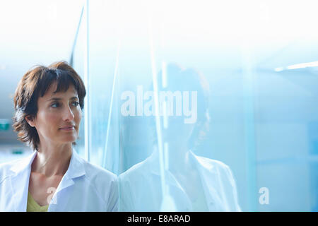 Confident mature businesswoman leaning against glass wall in office - Stock Photo