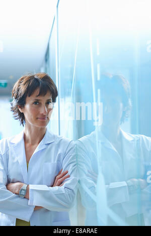 Portrait of mature businesswoman leaning against glass wall in office - Stock Photo