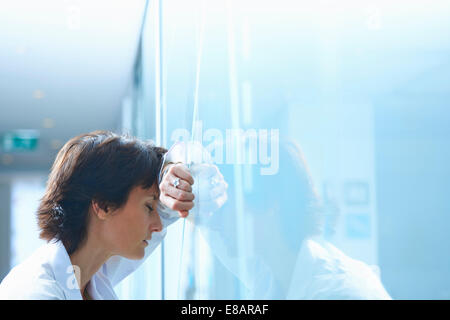 Mature businesswoman with eyes closed leaning against glass wall in office - Stock Photo