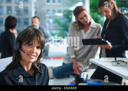 Portrait of female office worker using telephone headset in busy office - Stock Photo