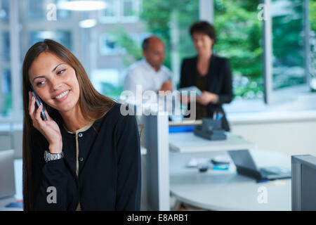 Businesswoman chatting on smartphone in office - Stock Photo
