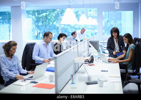 Business team at their desks in busy office - Stock Photo