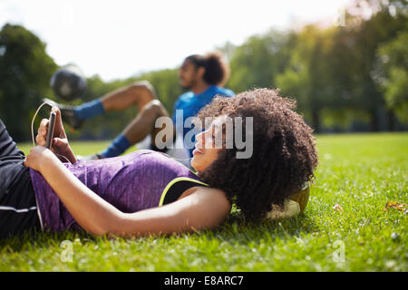 Young woman taking a break reading texts on smartphone in park - Stock Photo