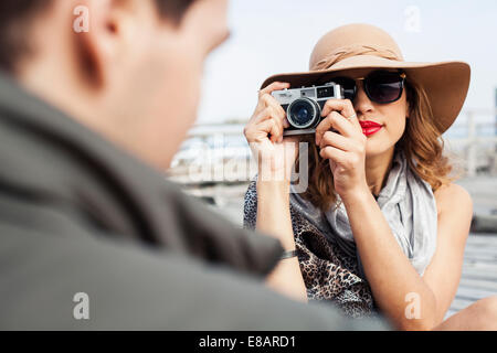 Young woman photographing boyfriend on coastal pier, Cape Town, Western Cape, South Africa - Stock Photo