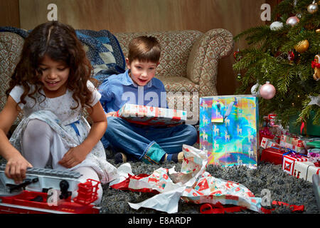Sister and brother in sitting room unwrapping and playing with christmas gifts - Stock Photo