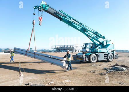 Two builders guiding girders on crane at construction site - Stock Photo