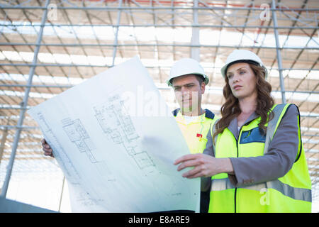 Site manager and architect looking down at blueprint on construction site - Stock Photo