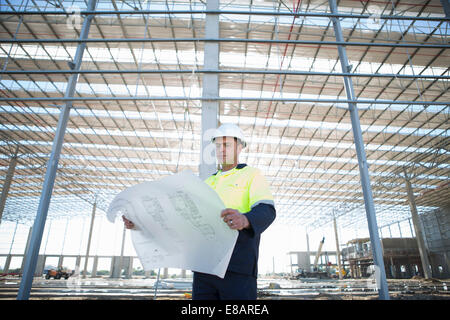 Site manager looking down at blueprint on construction site - Stock Photo