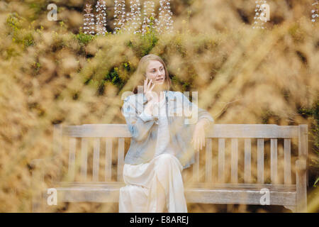 Young woman sitting on park bench chatting on smartphone in park - Stock Photo