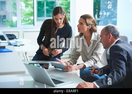 Three businessmen and women having informal meeting in office - Stock Photo