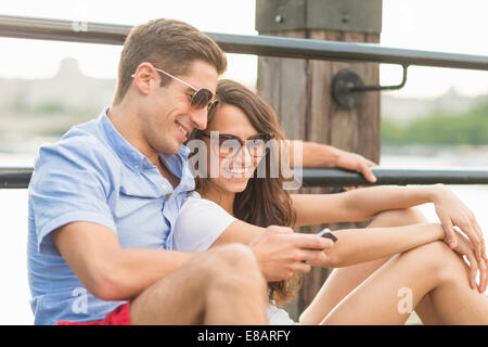 Young couple wearing sunglasses, man using cell phone - Stock Photo