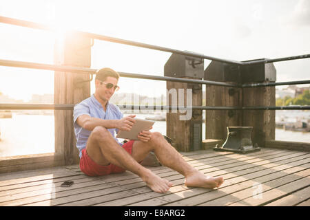 Young man sitting on pier using digital tablet - Stock Photo