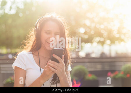 Young woman wearing headphones listening to music - Stock Photo