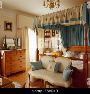 Cream sofa with blue cushions in front of glass french for Small four poster bed