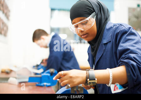 Female student using vice grip in college workshop