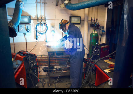 Male student welder welding in college workshop - Stock Photo