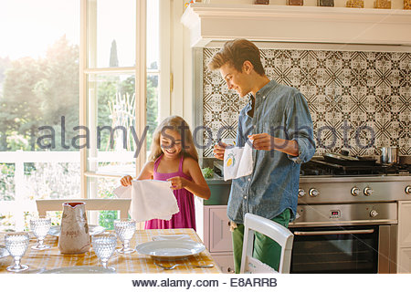 Brother and sister setting kitchen table - Stock Photo