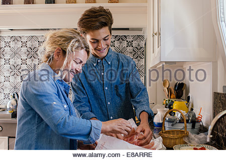 Grandmother and grandson preparing food in kitchen - Stock Photo