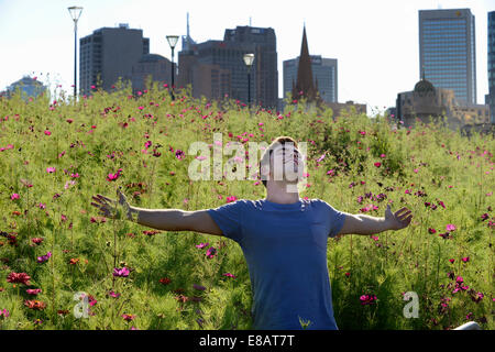 Young man, arms outstretched, against wild flowers and cityscape - Stock Photo