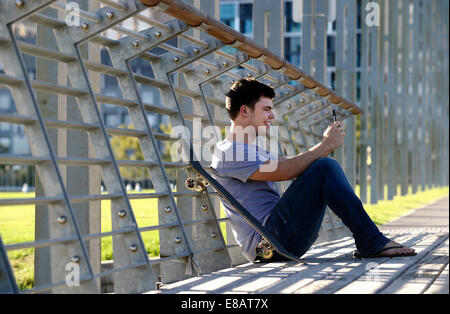 Young man sitting, using mobile phone, skateboard beside him - Stock Photo