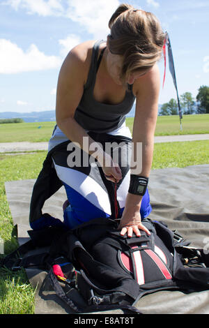 Female skydiver closing parachute container in field, Buttwil, Luzern, Switzerland - Stock Photo