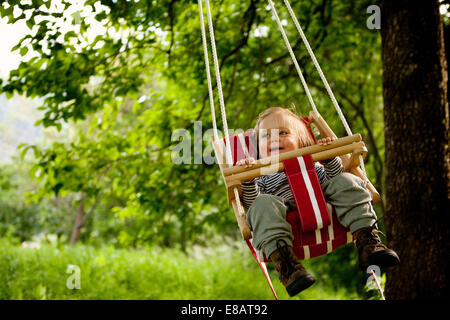 Young girl in swing, smiling - Stock Photo