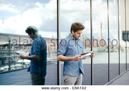 Young man reading newspaper by glass window - Stock Photo