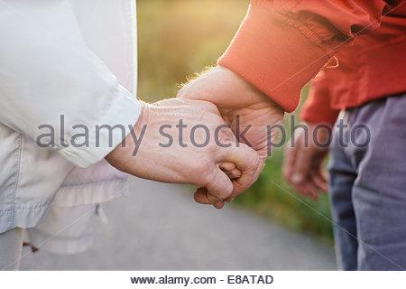 Senior couple holding hands, close up - Stock Photo
