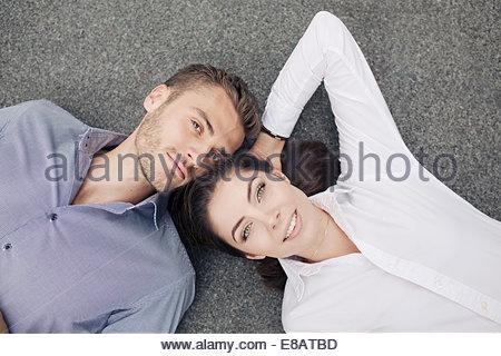 Young couple lying on floor, portrait - Stock Photo