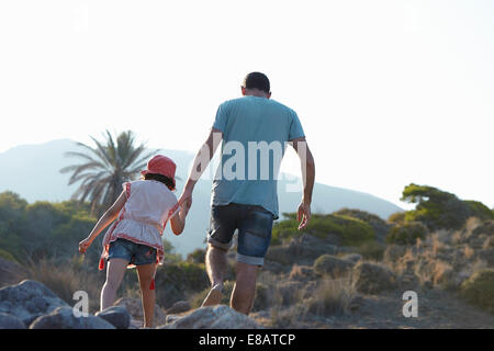 Father and daughter walking in hills hand in hand, Almeria, Andalusia, Spain - Stock Photo