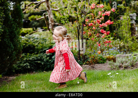 Young girl wearing gingham dress running in garden - Stock Photo