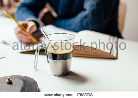 Coffee cup on table, man writing in background - Stock Photo