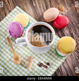 Cup of coffee and French macaroons on an old wooden table. - Stock Photo